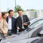 Man and Woman looking at car with car salesman