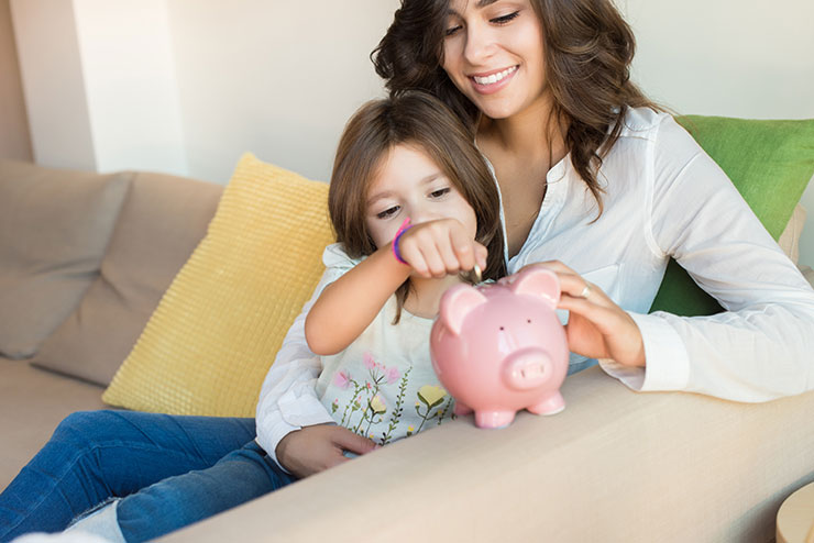Mom and daughter putting money into a piggy bank
