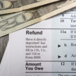 Two twenty dollar bills on top of a paper that talks about refunds.