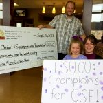 Family with FSU CU sign and giant check
